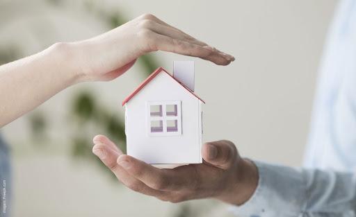 Pessoa protegendo uma casa como símbolo de segurança residencial