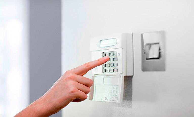 Pessoa controlando um alarme monitorado em uma residência
