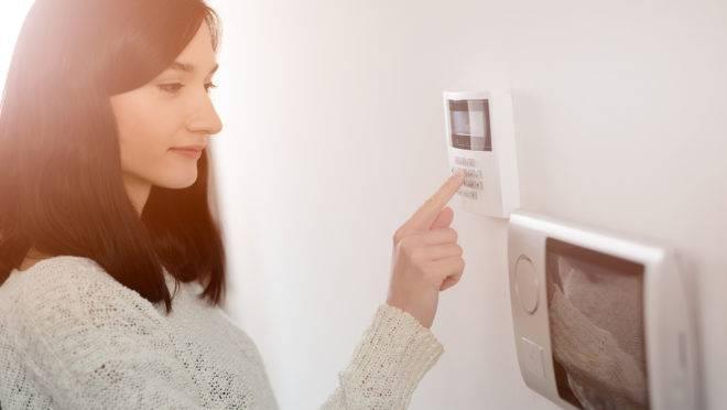Moradora de uma casa realizando a programação de alarme monitorado